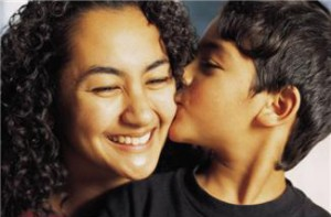 young boy kissing woman